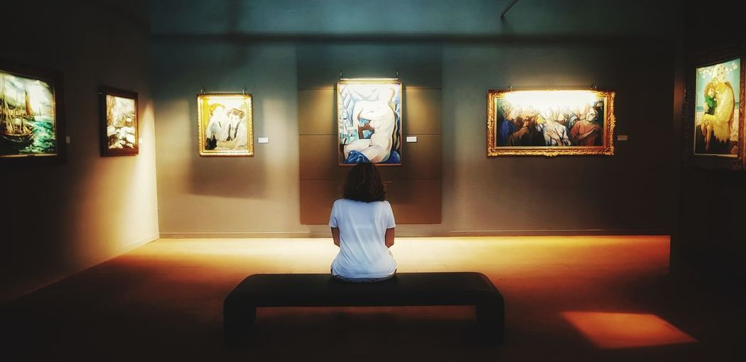 Rear view of woman sitting in museum