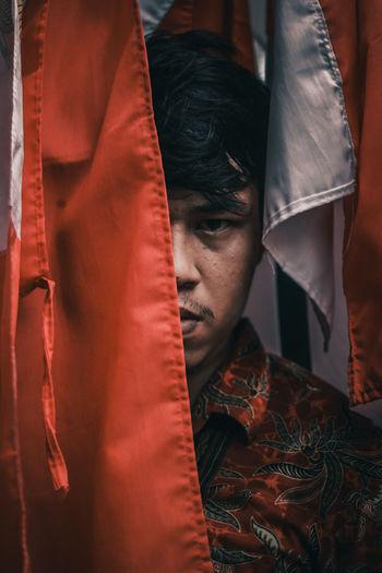 Close-up portrait of man behind textiles