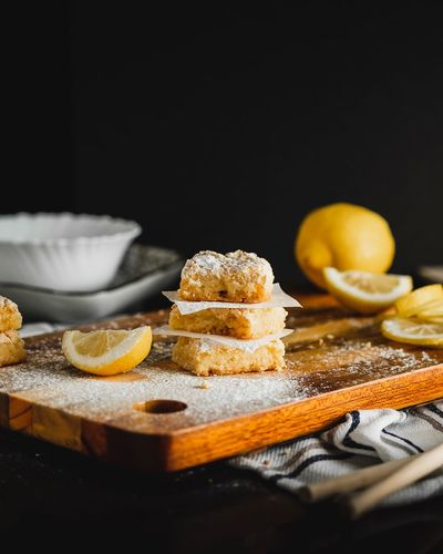 Lemon Squares Lemon Sweet Sugar Yellow Low Key Low Key Photography Dark Photography Lemon Squares  Lemon EyeEm Selects Food Food And Drink Freshness Healthy Eating Indoors  Table Still Life Citrus Fruit SLICE Fruit Sweet Food Cutting Board Orange Color Close-up Cake Selective Focus Ready-to-eat No People Kitchen Utensil