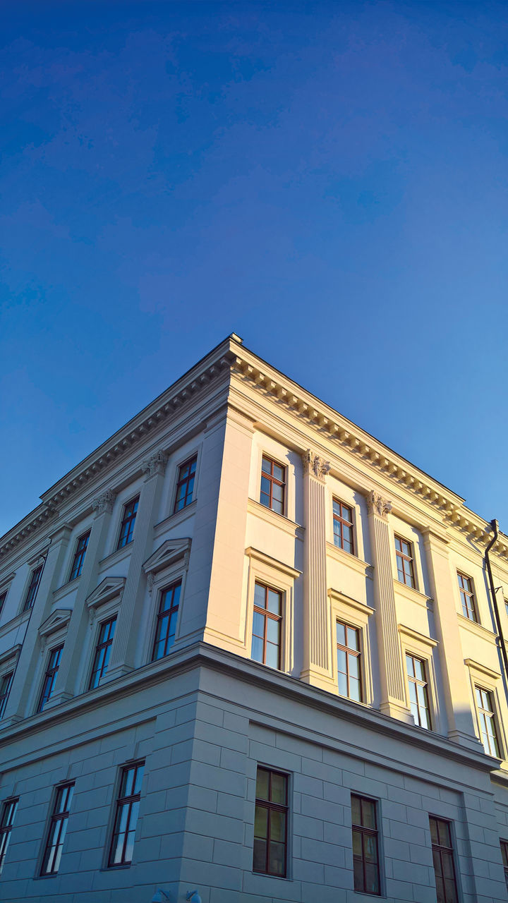 low angle view, architecture, building exterior, built structure, outdoors, window, sky, day, no people, blue, clear sky, modern, justice - concept, police station
