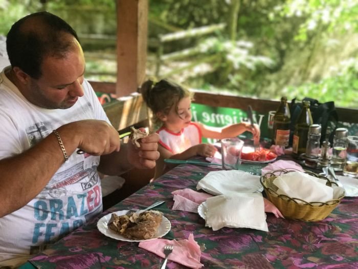 Father and daughter eating food at table in restaurant