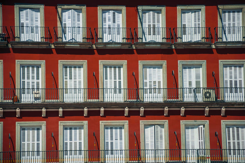 Old building with colorful facade and windows with balustrade on the plaza mayor in madrid, spain.