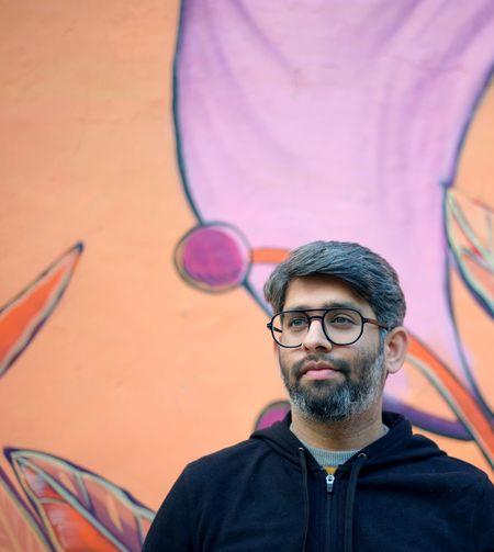 Man wearing eyeglasses looking away while standing against wall outdoors