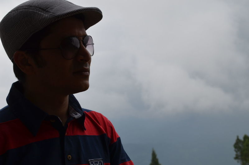 Man wearing sunglasses and cap while looking away against sky