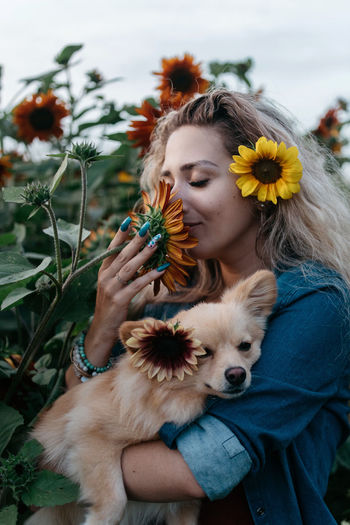 Woman carrying dog while smelling sunflower at farm