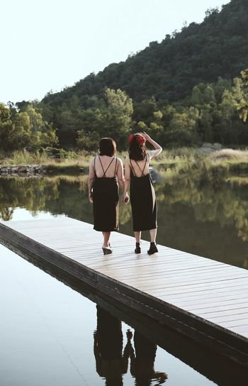 Rear view of women standing by lake against sky