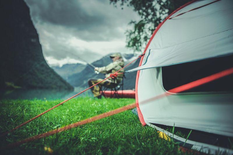 Tent at grassy lakeshore