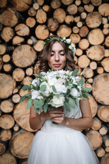 Young woman holding flower bouquet standing against logs