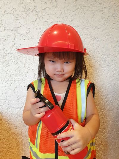 Portrait of girl wearing firefighter helmet while holding fire extinguisher against wall