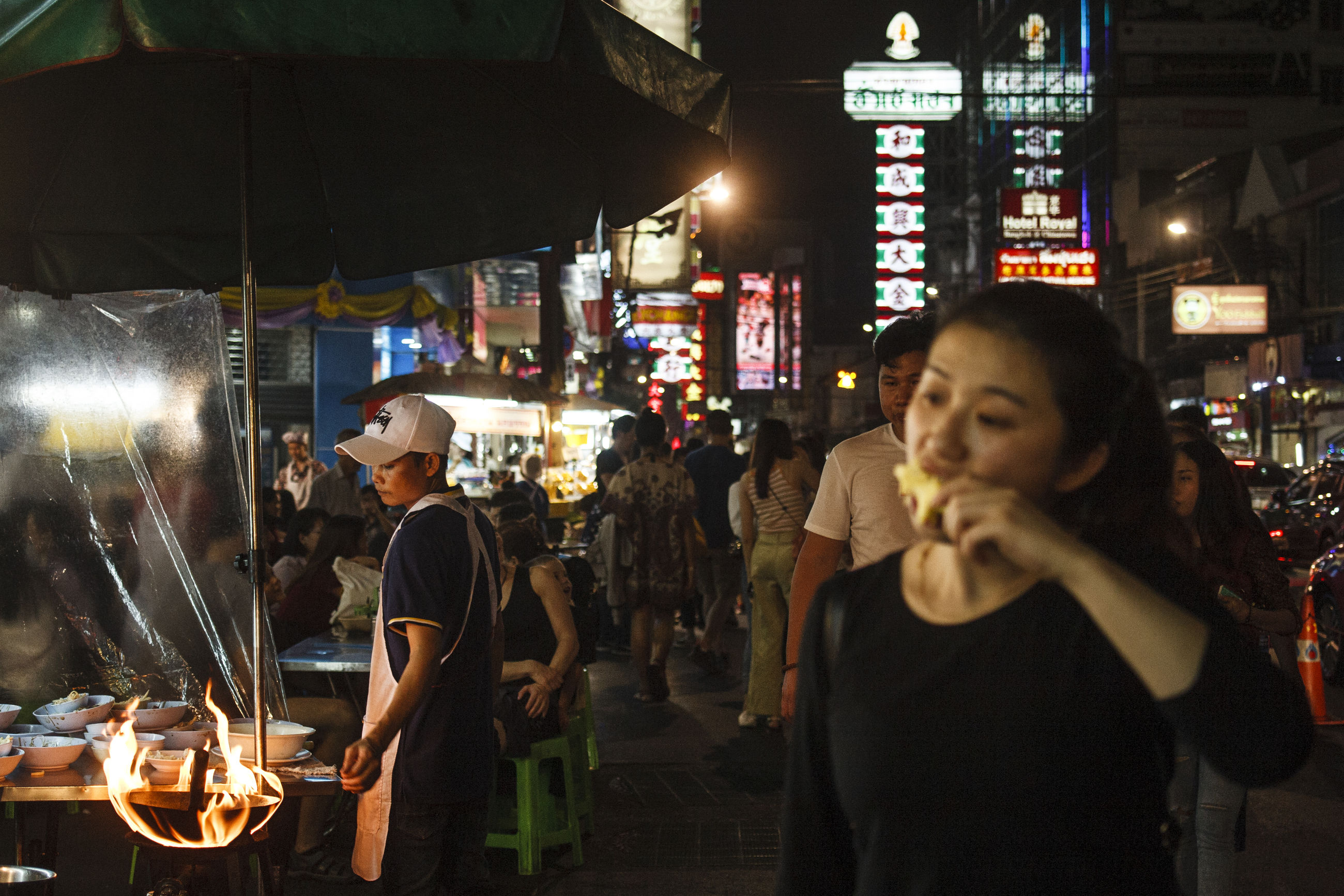 illuminated, night, real people, leisure activity, lifestyles, standing, incidental people, food and drink, city, architecture, people, group of people, young adult, communication, young women, built structure, women, front view, building exterior, holding, drinking