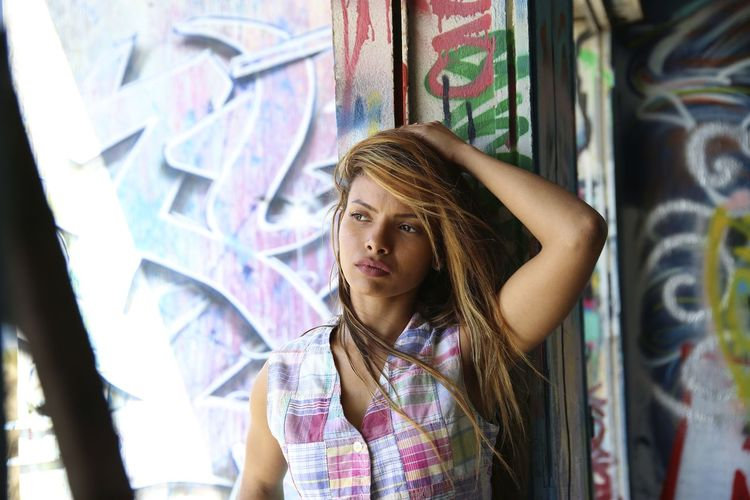 Portrait of teenage girl standing against graffiti