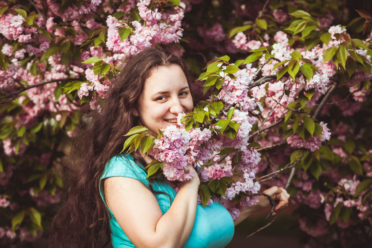 Smiling woman with pink flowers