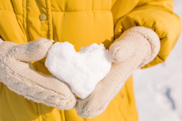 Close-up of hand holding yellow during winter