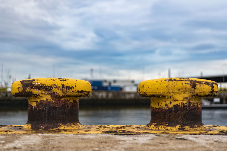 Rusty Yellow Bollards At Harbor