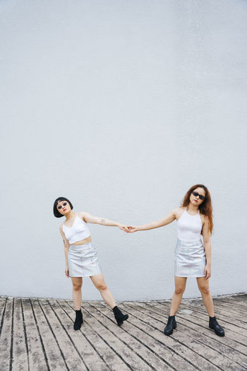 Full length of lesbian couple holding hands standing against wall outdoors