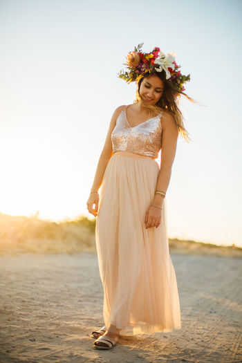 Woman Wearing Flowers Standing At Beach Against Sky