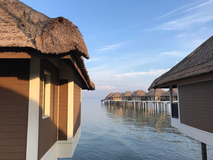 Stilt houses over sea against sky