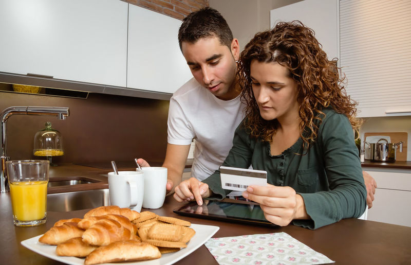 Portrait of young couple with electronic tablet and credit card buying on internet. Online shopping concept. Holding Interior Electronic Commerce Purchase Adult Two Leisure Family Paying Portrait Wireless Commerce Love Websurfing Female Male Caucasian Sitting Indoors  Young Ecommerce E-commerce Technology Buying People Smile Girl Weekend Coffee Cup Juice Orange Breakfast Lifestyle Happy Payment Shopping Internet Home Kitchen Woman Man Couple Online  Credit Card Card Credit Pad Electronic Tablet