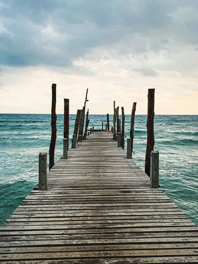 Wooden jetty on pier over sea against sky