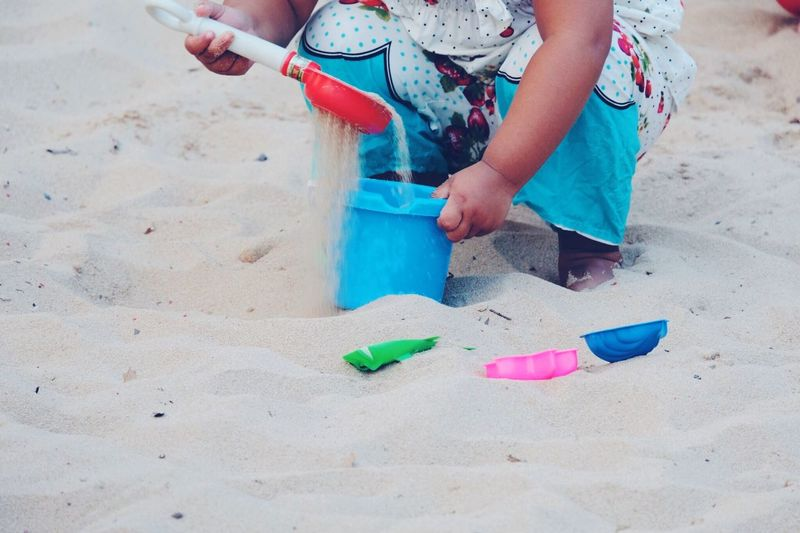 Low section of girl playing on sand at beach