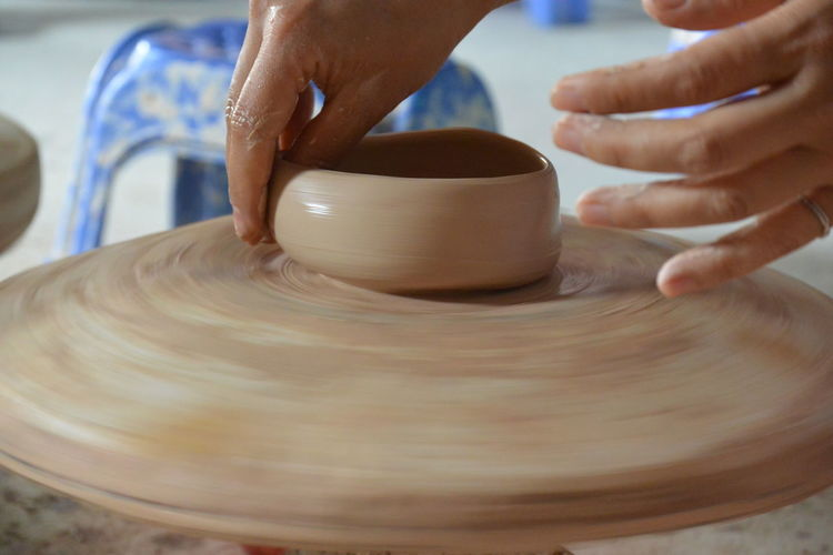 Cropped hands of person making pot in workshop