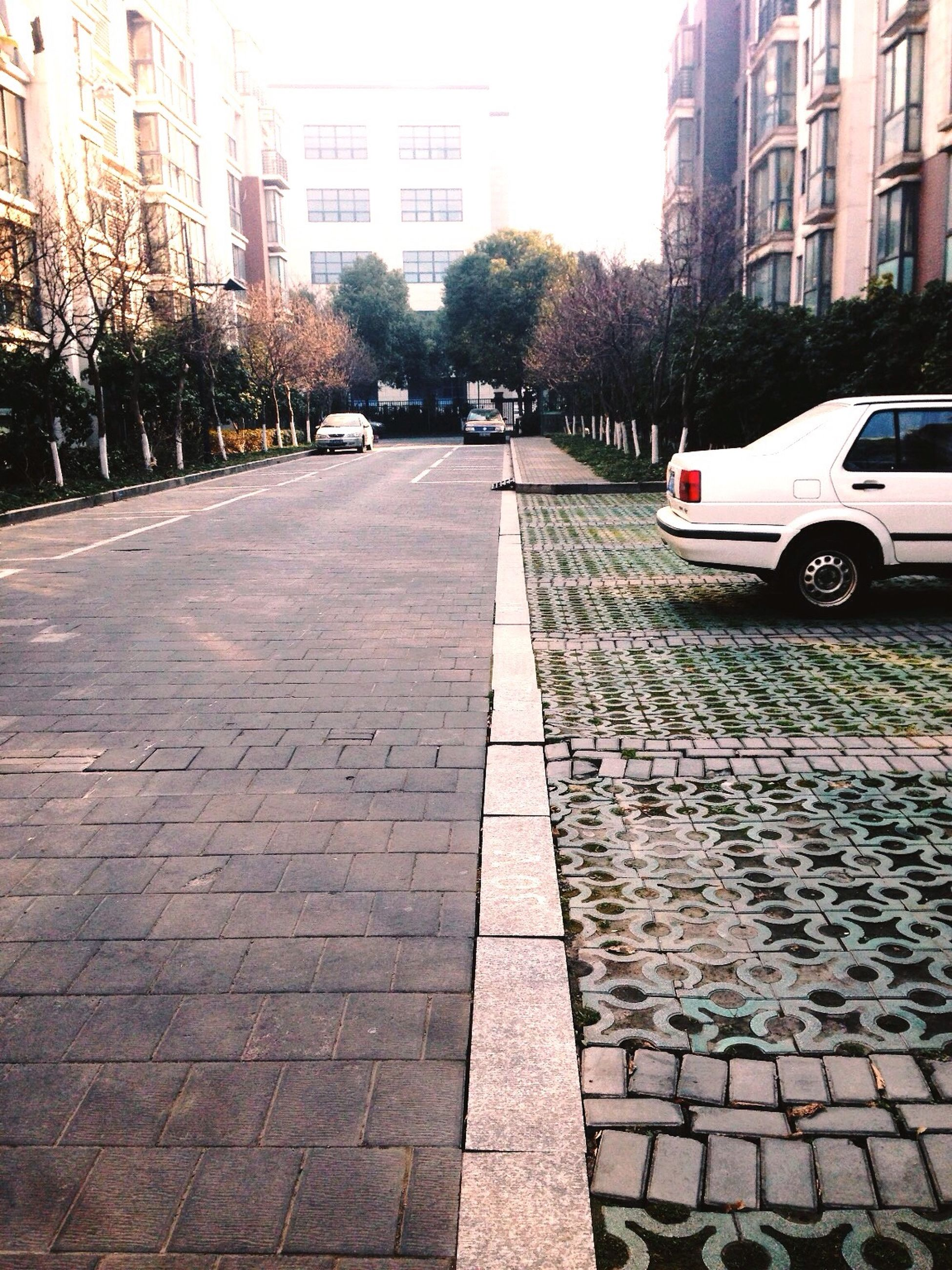 building exterior, architecture, built structure, city, street, the way forward, transportation, car, diminishing perspective, vanishing point, road, city life, building, incidental people, land vehicle, city street, road marking, cobblestone, mode of transport, day