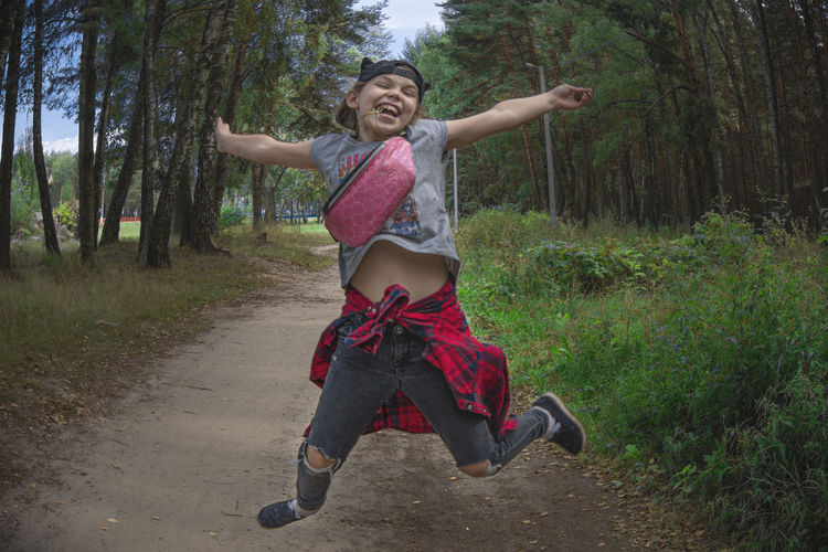 Full length of happy young woman in forest