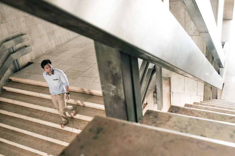 High Angle View Of Man Moving Down On Steps