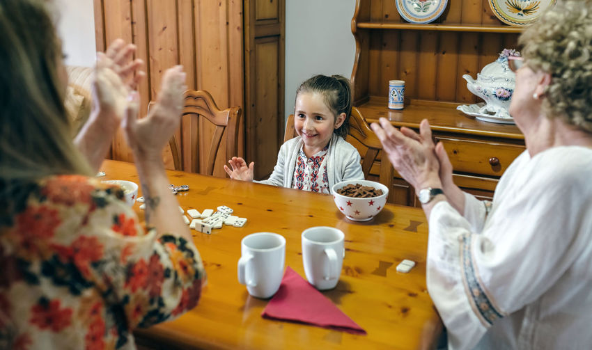 Little girl winning domino her mother and her grandmother Breakfast Domino Family Females Horizontal Stack Caucasian Child Childhood Cofee Daughter Dominoes Elder Game Generation Generations Girl Leisure Games Playing Real People Senior Table Three People Togetherness Women