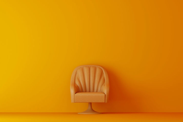 Empty chair against orange wall