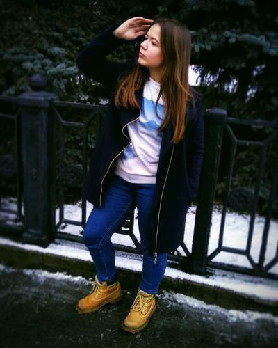 Fashionable Young Woman Posing By Railing During Winter