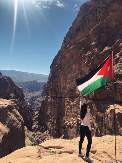 Woman holding jordanian flag on the top of the mountain in petra
