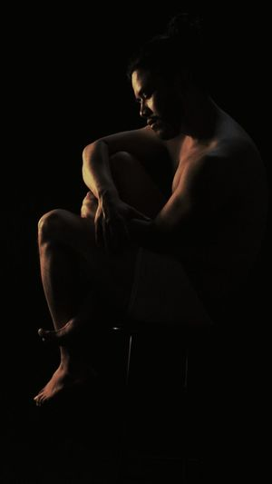 Rear view of silhouette man against black background