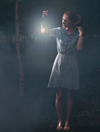 Full length of woman holding lit lantern at night