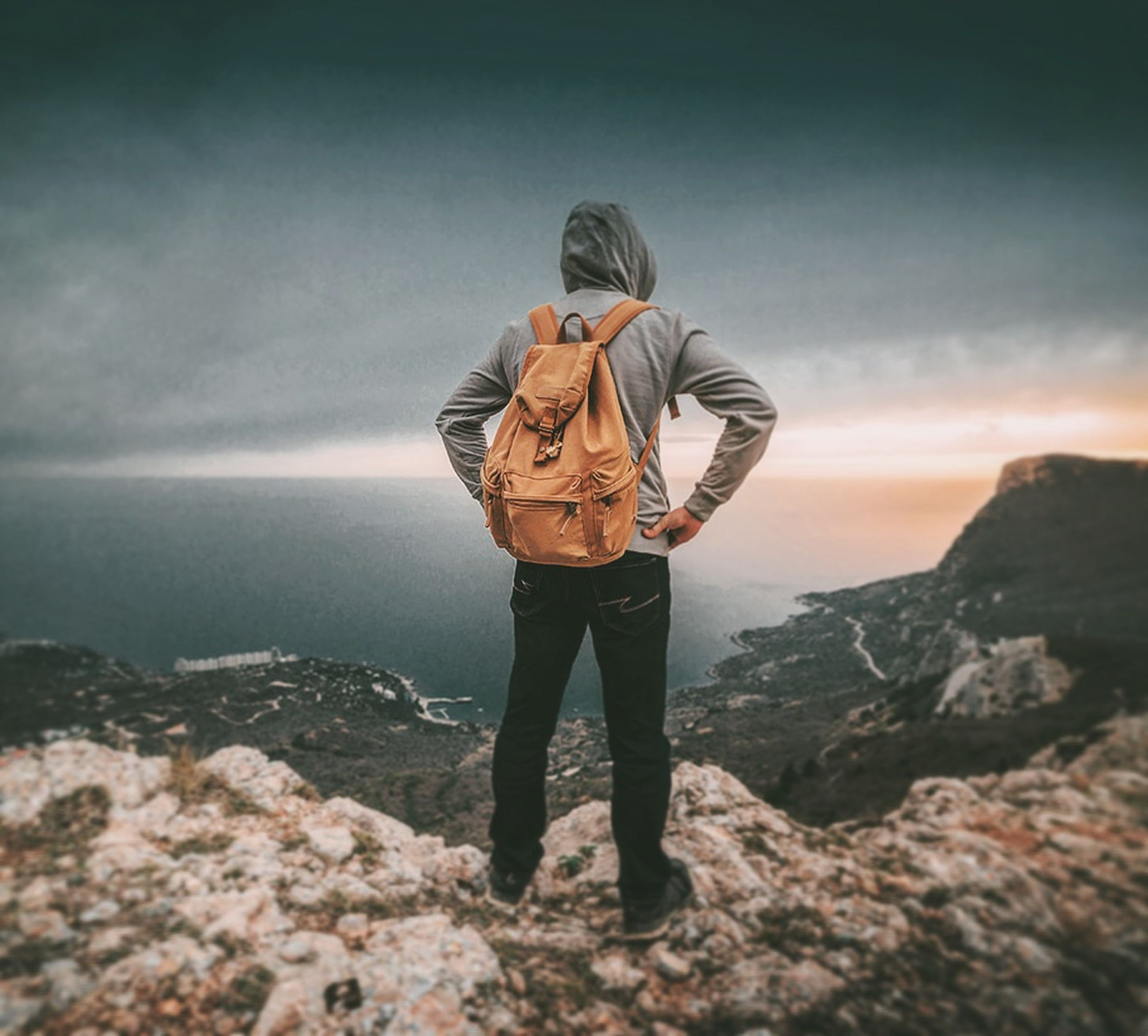 one person, standing, real people, full length, leisure activity, lifestyles, rear view, sky, casual clothing, beauty in nature, men, scenics - nature, cloud - sky, nature, rock - object, rock, solid, land, sea, outdoors, hood - clothing, looking at view