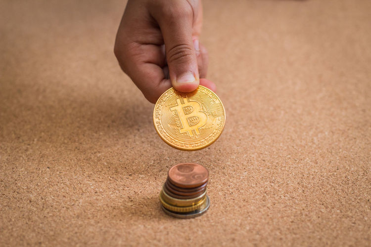 Close-up of hand holding bitcoin over stack on table