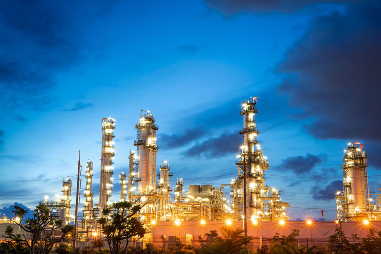 Chemical oil refinery plant, power plant and metal pipe on sunrise sky background.