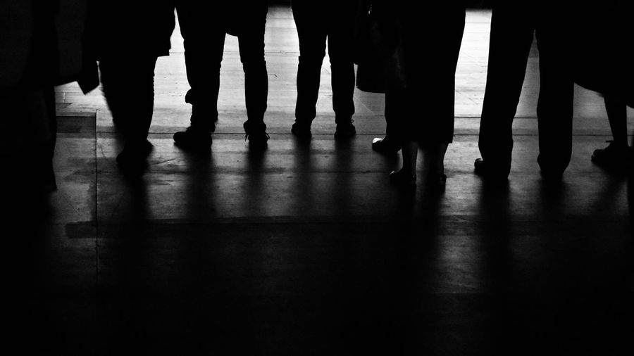 Low section of people standing on wooden floor