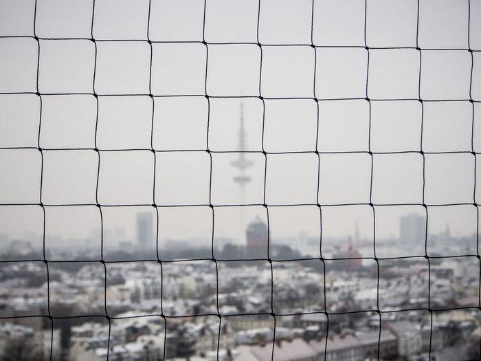 Buildings In Foggy Weather Seen Through Net