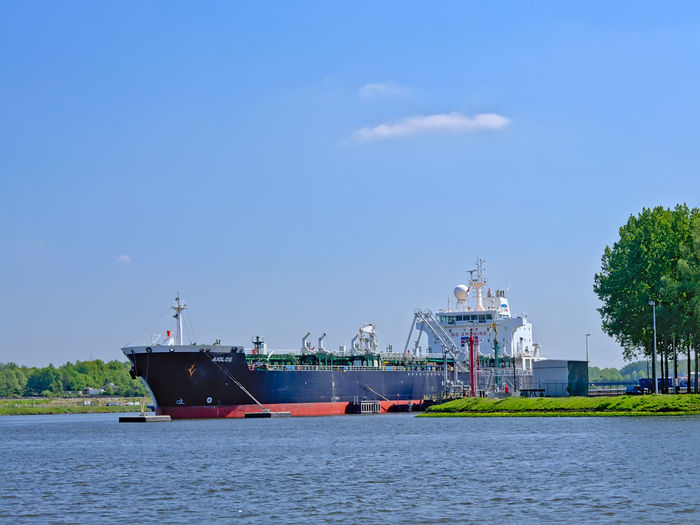 Freighter navigating Gent-terneuzen canal in the port of Ghent, Belgium Day Outdoors Ghent Belgium Harbor Portrait Scheldt River Waterway Ship Freighter Cargo Ship Transportation Industry Water Waterfront Nautical Vessel Shipping  Mode Of Transportation Nature Tree Environment Shipping  Dock Blue