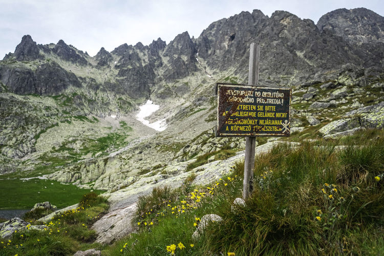 View of information sign on landscape against mountains