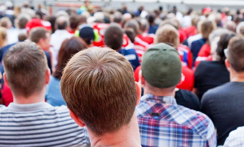 Crowd sitting on chair at stadium
