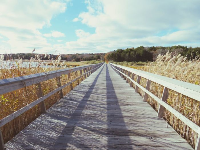 Footbridge over salt marsh  against sky