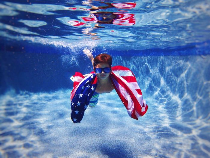 Portrait of cute boy with american flag swimming under pool