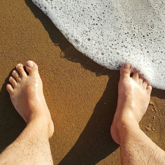 Close-Up Of Bare Feet At Waters Edge