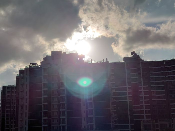 Low angle view of sunlight streaming through buildings