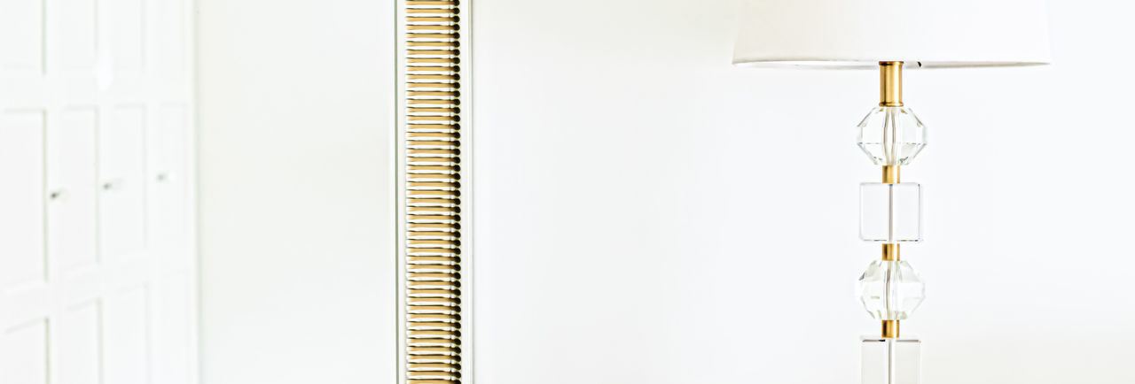 Close-up of electric lamp on table against white background