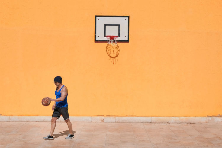 Basketball - Sport Sport One Person Basketball Hoop Full Length Playing Exercising Basketball Player Sportsman Athlete Ball Basketball - Ball Court Lifestyles Healthy Lifestyle Leisure Activity Motion Young Adult Men Skill  Basketball Uniform Effort Copy Space Yellow Yellow Wall My Best Photo