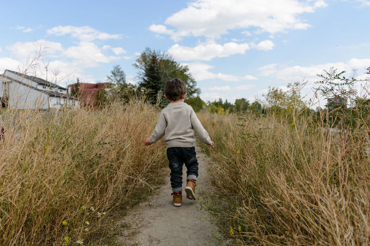 Rear view of boy on dirt road against sky