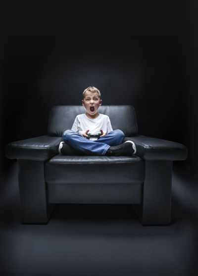 young boy in armchair watching TV and is screaming with a controller in his hand Couch Fear Gaming Young Age Boy Child Childhood Computer Danger Elementary Age Front View Indoors  Looking At Camera Night One Person Playstation Screaming Shouting Sitting Spooky Studio Shot Television Terrified Videogames